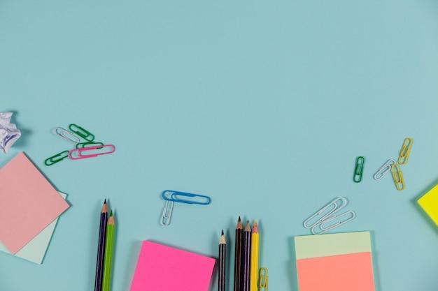 Crayons de couleur, notes autocollantes et épingles à papier