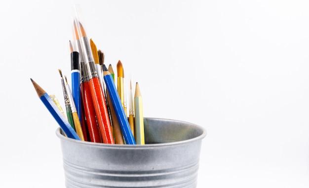 Crayons de couleur et pinceaux à dessiner dans un bocal, arrière-plan