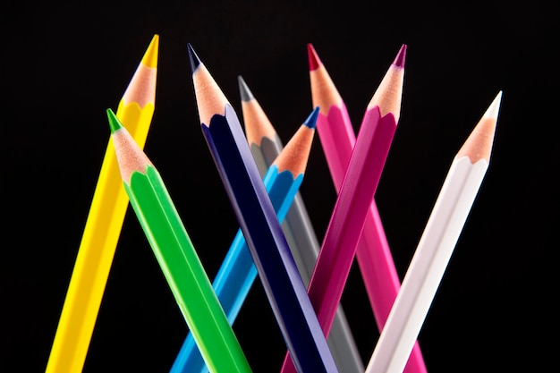 Crayons de couleur pour dessiner sur un fond sombre. éducation et créativité. loisirs et art