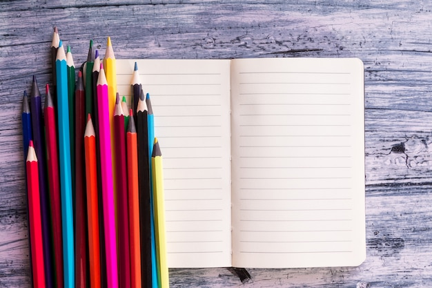 Crayons de couleur près de note sur fond en bois. vue de dessus. espace de copie.