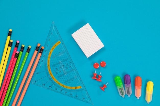 Crayons de couleur, règle triangulaire transparente, tas de papier à gratter blanc, un groupe de punaises rouges