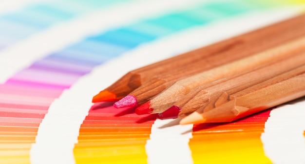 Crayons de couleur rouge et rose et nuancier de toutes les couleurs