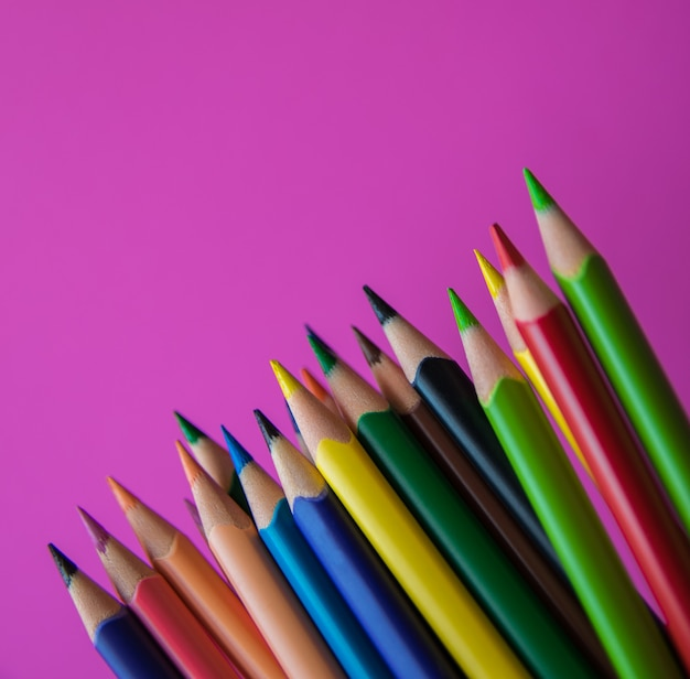 Crayons de couleur sur la surface rose. fermer.