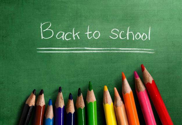 Crayons de couleur avec le texte de la rentrée scolaire sur fond vert