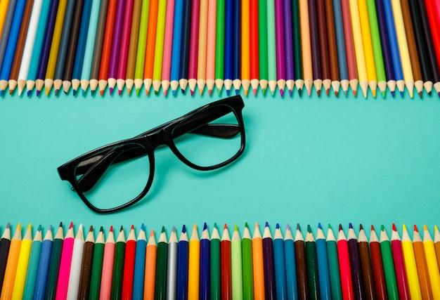 Crayons de couleur et verres sur table bleue.