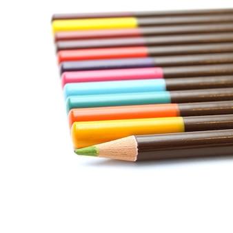 Crayons de couleur et un vert unique sur fond blanc
