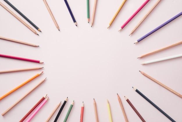 Crayons de couleur vive alignés autour du périmètre du fond rose.
