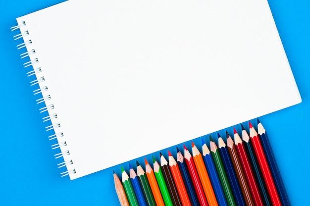 Crayons de couleurs arc-en-ciel et cahiers sur une table bleue
