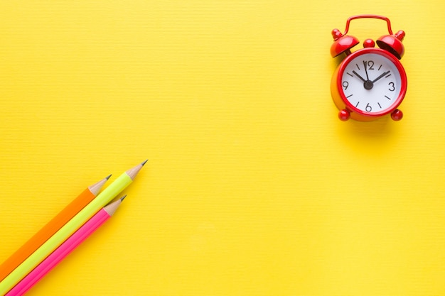 Crayons de couleurs vives et réveil sur jaune.