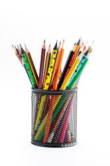Crayons à dessin en graphite bordés de couleurs vives à l'intérieur d'un panier noir sur un bureau blanc