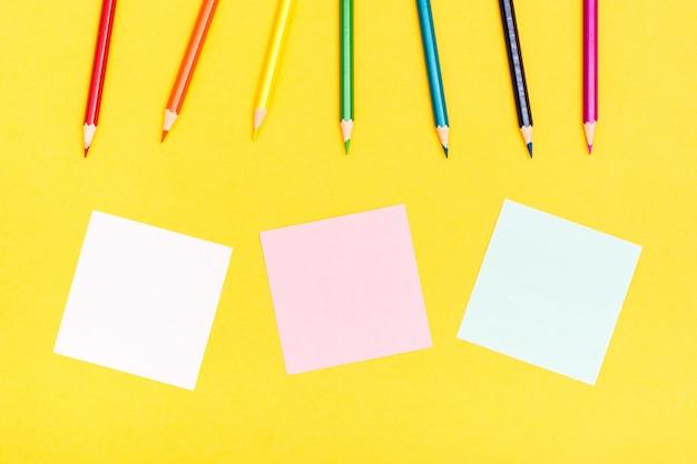 Crayons et feuilles de bois colorés pour écrire sur un fond jaune