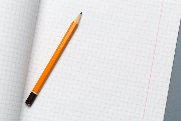 Crayons et feuilles de papier avec bloc-notes sur une table de bureau grise