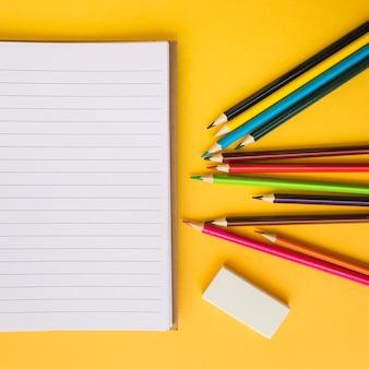 Crayons gros plan et caoutchouc près du bloc-notes