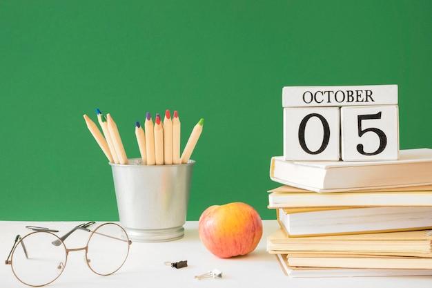Crayons de jour de l'enseignant heureux et pile de livres