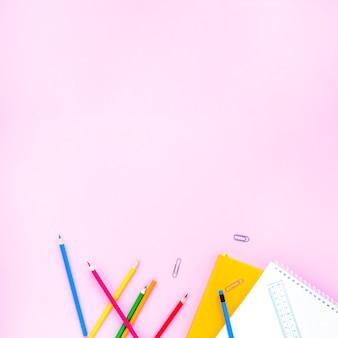 Crayons lumineux et cahiers posés au hasard