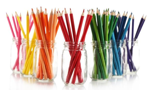 Crayons lumineux dans des bocaux en verre, isolés sur blanc