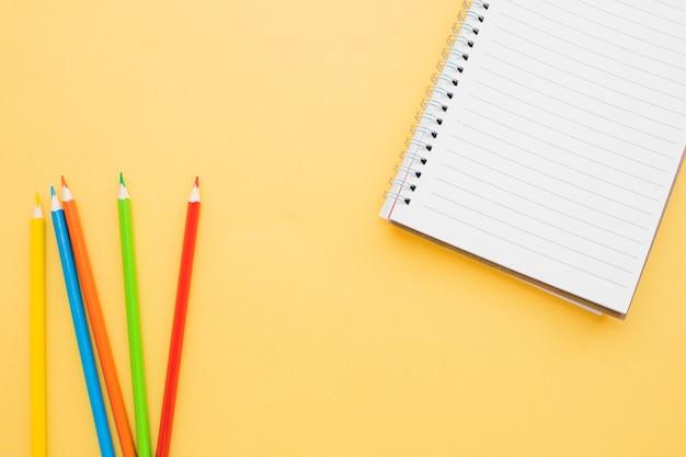 Crayons lumineux près de joli cahier