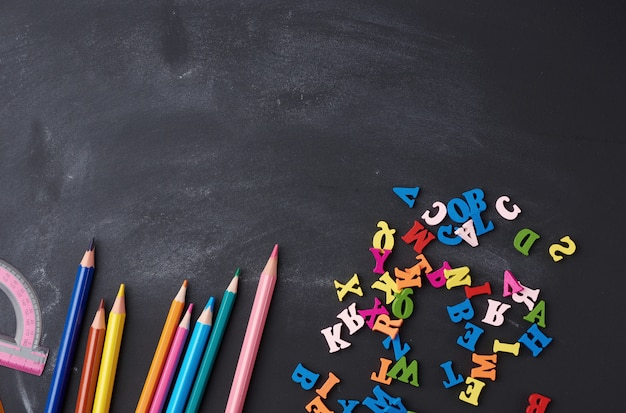 Crayons multicolores en bois, lettres sur une planche de bois noire