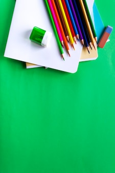 Crayons multicolores, cahiers, gomme et taille-crayon sur fond vert