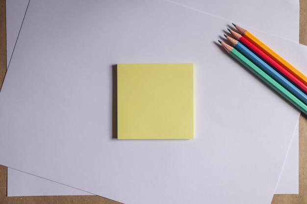 Crayons multicolores et cahiers marron sur fond blanc
