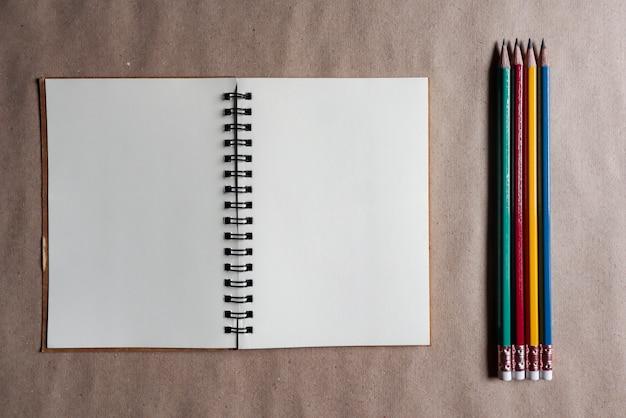 Crayons multicolores avec des notes marron sur papier brun