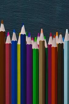 Les crayons multicolores se trouvent sur un fond texturé noir.
