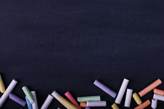 Des crayons multicolores se trouvent sur un tableau noir