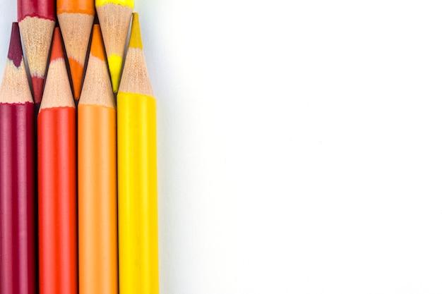 Crayons orange et jaunes sur fond blanc