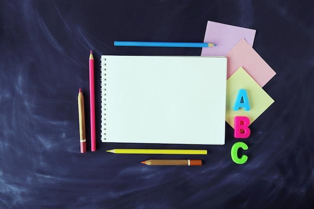 Crayons papier et carnet de croquis sur fond de tableau vue de dessus espace copie retour à l'école
