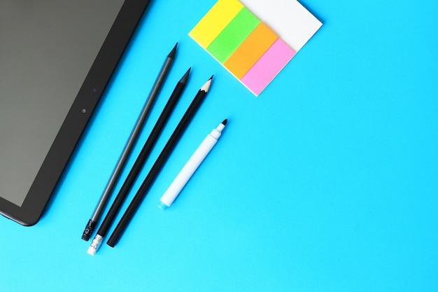 Crayons, papier à lettres et tablett sur fond bleu et retour au concept de l'école.