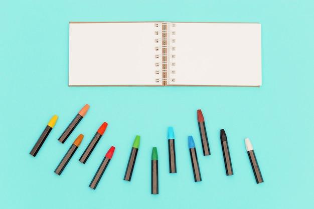 Crayons pastel à l'huile et cahier ouvert au printemps pour les croquis lieu de travail de l'artiste