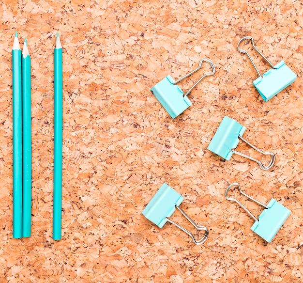 Crayons et pinces pour reliures sur une table en bois