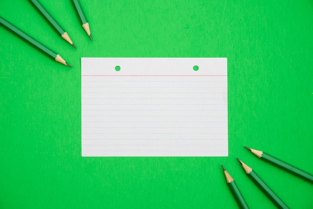 Crayons pointus et papier à lignes texturé sur fond vert clair