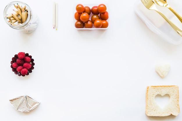 Crayons près de la boîte à lunch et de la nourriture