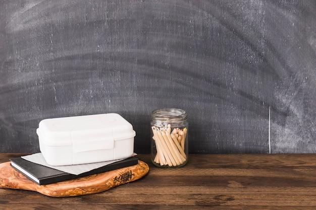 Crayons près de la boîte à lunch en plastique et cahier