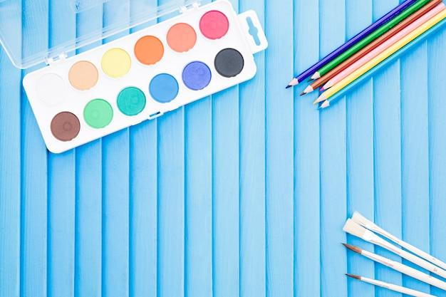 Crayons près des pinceaux et aquarelle