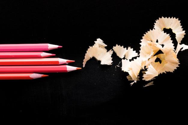 Crayons roses sur tableau noir