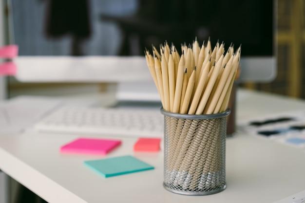 Les crayons sont dans la boîte en filet et placés sur le bureau
