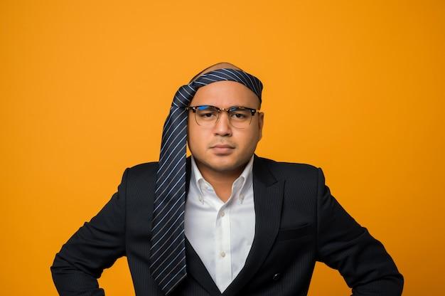 Crazy business homme chauve gueule de bois portant une cravate sur la tête avec une expression sérieuse sur le visage