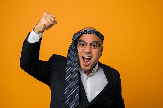 Crazy business homme chauve gueule de bois portant une cravate sur la tête lever son poing sur jaune