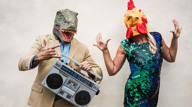 Crazy senior couple dancing at carnival party wearing t-rex and chicken mask - old trendy people having fun listen music with boombox stereo - absurd and funny trend concept - focus on faces