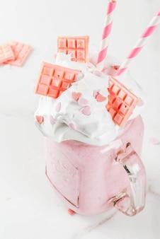 Crazy shake, milkshake romantique pour la saint-valentin avec des coeurs de fraise, de chocolat blanc et de sucre candi, sur fond blanc, copyspace close view