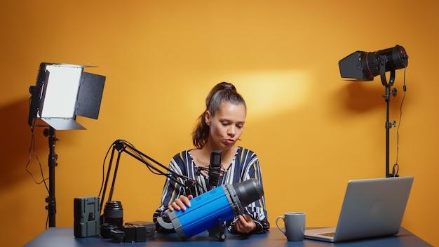 Créateur de contenu faisant un examen en ligne de la lumière de studio professionnelle. influenceur des médias sociaux créant du contenu internet en ligne sur l'équipement vidéo professionnel pour les abonnés web et la distribution