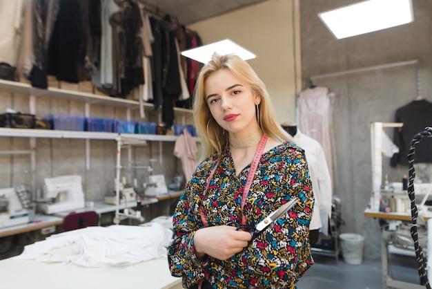 Créateur de mode avec des ciseaux dans ses mains se tient dans un studio de mode et pose devant la caméra.