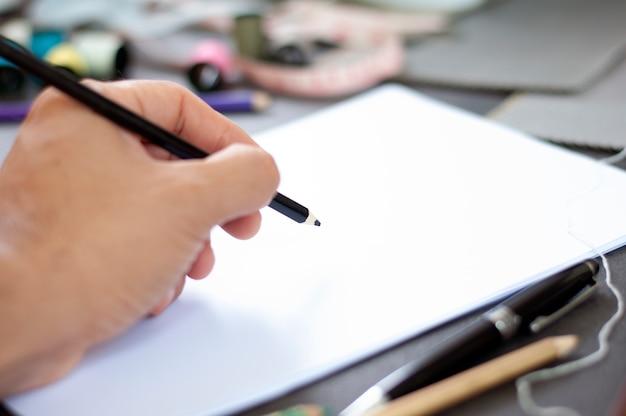 Créateur de mode croquis sur papier vierge à l'atelier.