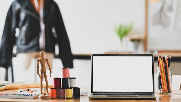 Créateur de mode de l'espace de travail avec ordinateur portable, fil, crayon et bois factice sur le bureau.