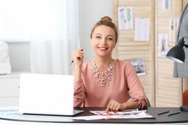 Créateur de mode féminin avec ordinateur portable travaillant en studio