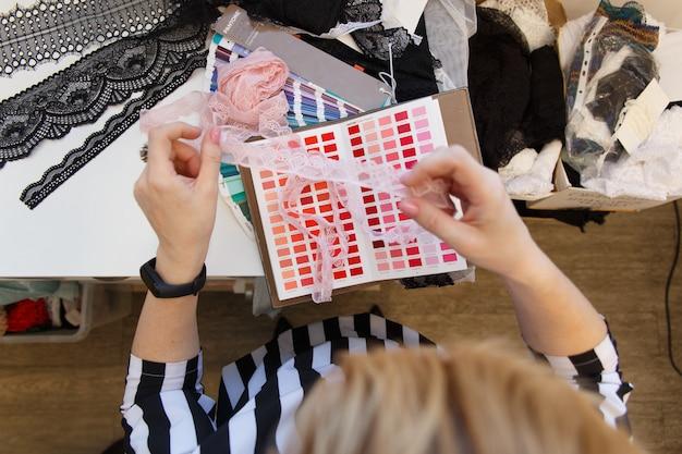 Créateur de mode féminine tenant des échantillons de couleur en choisissant le textile en tissu sur le lieu de travail, couturière ou tailleur travaillant au bureau en pointant sur la palette de sélection de choix, vue en gros