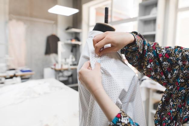 Un créateur de mode insère des aiguilles dans les vêtements d'un mannequin.