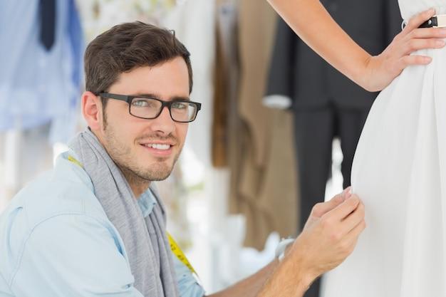 Créateur de mode masculin ajustant la robe sur le modèle